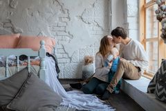 Happy parents sit on the windowsill in their bedroom and kiss, next to crawling their little son.  royalty free stock photos