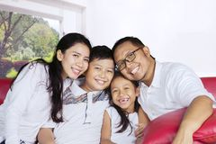 Happy family laughing together on the couch Royalty Free Stock Photos