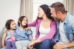 Happy parents sitting with daughters on sofa Stock Photos
