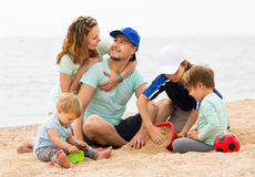 Happy parents smiling with children resting at sea Stock Photos
