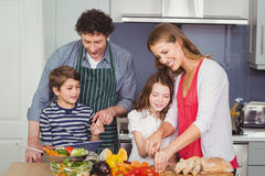 Happy parents with son and daughter in kitchen. Happy parents standing with son and daughter in kitchen at home Stock Photography