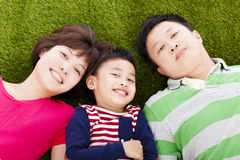 Happy parents and son lying on a meadow. In the park stock image