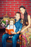 Happy parents and son reading a book, family leisure Royalty Free Stock Photography