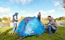 Happy parents and son setting up tent at campsite. Camping, tourism and family concept - happy mother, father and son setting up tent at campsite royalty free stock photo