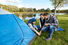 Happy parents and son setting up tent at campsite. Camping, tourism and family concept - happy mother, father and son setting up tent at campsite stock photos