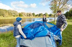Happy parents and son setting up tent at campsite royalty free stock photo