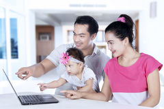 Happy parents teaching daughter with laptop. Portrait of happy parents teaching daughter by using laptop while sitting at home stock image