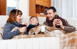 Happy parents and teenage son warming near warm calorifer Stock Photo