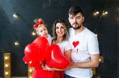 Happy parents and thair baby daughter on saint valentine`s day stock photo