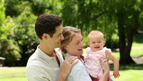 Happy parents with their baby girl in the park Royalty Free Stock Photo