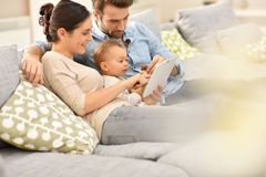 Happy parents with their baby girl using tablet Stock Photos