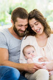 Happy parents with their baby in living room Stock Image