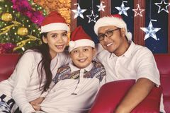 Parents and child celebrating Christmas at home Stock Images