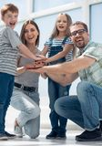 Happy parents and their children built a tower out of their hands. Family team concept royalty free stock photos