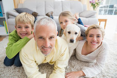 Happy parents with their children and puppy on floor Stock Photography