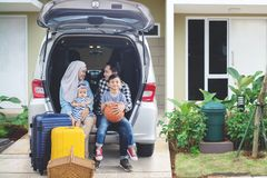 Happy family ready for vacation. Happy parents with their children ready for vacation while sitting together in the car trunk. Shot in the house garage Royalty Free Stock Images