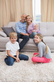 Happy parents with their children on sofa Stock Image