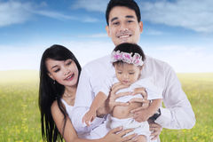 Happy parents and their kid at field Stock Image