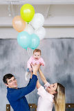 Happy parents and their little daughter. Portrait of a young family with balloons. royalty free stock images