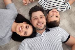 Happy parents and their son lying together on floor. Family time royalty free stock image