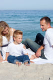 Happy parents with their son sitting on the sand. At the beach Stock Photos