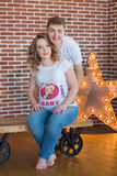 Happy parents-to-be couple looking at a cute red baby shoes for their unborn child, indoors studio portrait Stock Photos