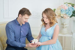 Happy parents-to-be couple looking at a cute red baby shoes for their unborn child, indoors studio portrait Stock Image