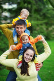 Happy parents with twins. Portrait of happy young parents with their two babies twins having fun in park Stock Images