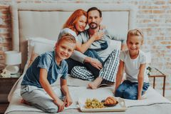 Happy parents and two kids having breakfast stock photos