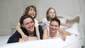 Happy Parents and Two Laughing Kids are Lying on the White Bed Having Fun Together During Weekend at Home. Young Couple. With Charming Smiles Spending Free Time stock video