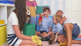 Happy parents and two little boys playing with hand puppets. Slow motion shot. Professional shot in 4K resolution. 092. You can use it e.g. in your commercial stock footage