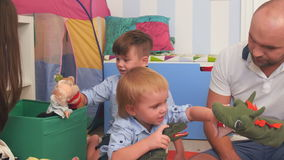 Happy parents and two little boys playing with puppets stock footage
