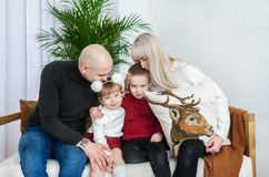 Happy parents with two little children indoors stock photography