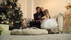 Happy parents with young children near the Christmas tree stock footage