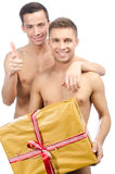Happy partners and a gift. Two beautiful guys. Love and relationships. Passion and hatred. Studio. Backgrounds royalty free stock photo