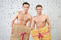 Happy partners and a gift. Two beautiful guys. Love and relationships. Passion and hatred. Studio. Backgrounds royalty free stock images