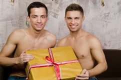 Happy partners and a gift. Two beautiful guys. Love and relationships. Passion and hatred. Studio. Backgrounds stock photo