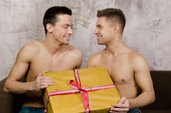 Happy partners and a gift. Two beautiful guys. Love and relationships. Passion and hatred. Studio. Backgrounds stock image
