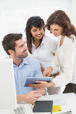 Happy partners using digital tablet together Stock Photo