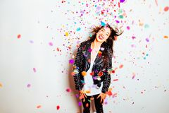 Happy party woman with confetti. Happy young and beatiful woman with fashion leather jacket enjoying the party with confetti stock photography
