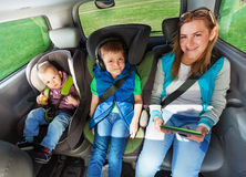 Happy passengers sitting on the backseats of a car Royalty Free Stock Photography