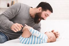 Father tickling and snuggling his baby son. Happy paternity leave. Daddy playing with his baby son, tickling him on bed at home stock photos