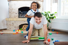 Happy paternity moments. Portrait of lovely family: cheerful Caucasian father looking at camera with wide smile and standing on his knees while his little mixed stock photo