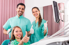 Happy patient and dental clinic crew Royalty Free Stock Image