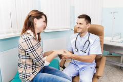 Happy patient at the doctor. Young woman in a doctor's office stock image