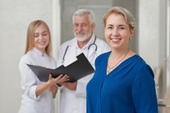 Happy patient and doctors posing, smiling. royalty free stock images
