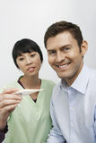 Happy Patient With Female Doctor Looking At Thermometer Royalty Free Stock Photography