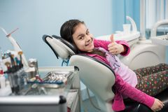 Happy patient girl showing thumbs up at dental clinic office. Medicine, stomatology and health care concept Royalty Free Stock Images