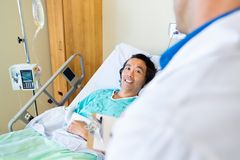 Happy Patient Looking At Doctor While Lying On Royalty Free Stock Photos