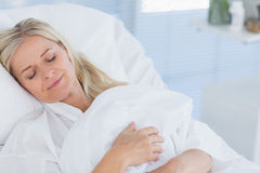 Happy patient lying on her bed Stock Photos